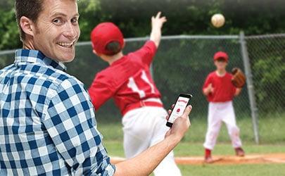 man checking his phone while watching children playing ball